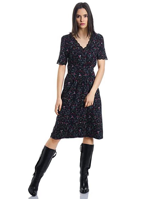 Ansicht ganzes Kleid, schwarzes Kurzarmkleid mit wellenförmigem Spitzenbesatz am Dekoltee, am Kleid befinden sich Blumen und Paradiesvögel in rot und türkis, um die Taille ist das Kleid abgenäht, man kann es am Rücken binden, es ist knielang und leicht ausgestellt