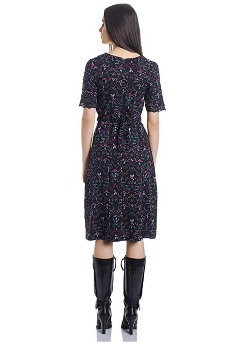 Ansicht von hinten, schwarzes Kurzarmkleid mit wellenförmigem Spitzenbesatz am Dekoltee, am Kleid befinden sich Blumen und Paradiesvögel in rot und türkis, um die Taille ist das Kleid abgenäht, man kann es am Rücken binden, es ist knielang und leicht ausgestellt
